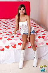 Sitting On Edge Of Bed Wearing Short Skirt In Boots