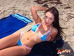 Sunbathing On Beach Towel Wearing Bikini Pushing Her Long Hair Back