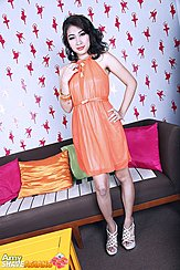 Amy With Hand On Hip In Orange Dress Wearing High Heels