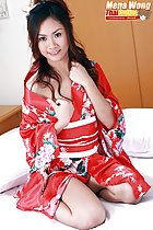 Kneeling on bed wearing red kimono