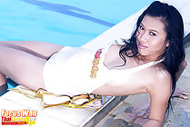 Reclining on edge of pool white top clinging to her body