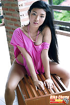 Sitting on bench wearing pink dress long hair over her shoulder