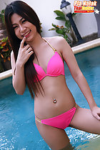Finger raised to her lips in swimming pool wearing bikini