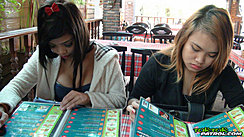 Two Girls Seated Together In Restaurant Reading Menus