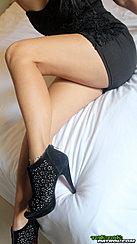 Mina Sitting On Bed Knee Drawn Up Wearing High Heels