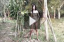Pla Pattama applying lotion outdoors topless in field